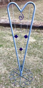 """Hearts and Diamonds"" Trellis. Light gray heart with chrome cross bars and dark purple accents. $395, Size: 65.5"" x 25"" x 25"" Available at Noyes Art Gallery, 119 S. 9th, Lincoln, NE 68508, 402-475-1061. Materials: planter base, tube, rod, candle holders, pipe cutouts, paint"