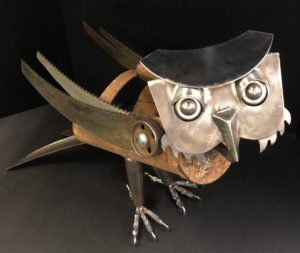"""Harrison Owl""$175, 21"" x 15"" x 13"" 7 lbs., available at Noyes Art Gallery, 119 S. 9th, Lincoln, NE 68508, 402-475-1061. Materials: grain scoop, ball bearings, steel wheels. hand spade handles, saw blades, kitchen chopper, mortar hoe, valve cap shields, carriage bolts, nuts, washers."