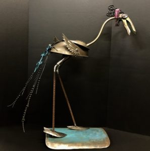 """Penelope Peacock"" 32"" x 14"" x 25"" 7 lbs. $135. Available at Noyes Art Gallery, 119 S. 9th, Lincoln, NE 68508, 402-475-1061. Materials: Lamp shade and base, hand clipper handles, hand spades, electric fence posts, saw blades, wall decor, candle holder, scrap metal, turquoise metallic paint, pink paint, black paint."